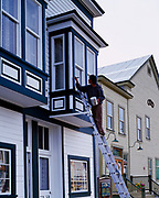 Dawson City resident Kim Biernaskie painting trim on Ruby's Place, a house of prostitution from era of the Klondike Gold Rush through the 1960s, Parks Canada, Dawson City, Yukon Territory, Canada.