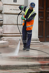 © Licensed to London News Pictures. 03/10/2019. London, UK. Workers clean up at the Treasury in Westminster after it had been sprayed with red paint by Extinction Rebellion activists . The stunt, which partly went wrong, was intended to cover the building in red dye looking like blood. Photo credit: Peter Macdiarmid/LNP