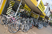 In Apeldoorn staan voor een fietswinkel nieuwe en tweedehands fietsen opgesteld.<br /> <br /> In Apeldoorn new and used bikes are lined up for a bike shop.