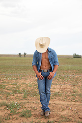 hot cowboy with an open shirt leaning against a fence on a ranch