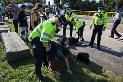 Metropolitan Police officers restrain human rights activists trying to stop a convoy of trucks delivering military equipment to ExCeL London for the DSEI 2021 arms fair on 8th September 2021 in London, United Kingdom. The third day of week-long Stop The Arms Fair protests outside the venue for one of the world's largest arms fairs was themed around demilitarising education.