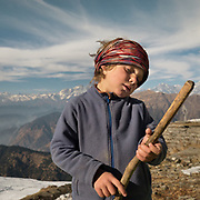 A child holds a wooden stick like a guitar.