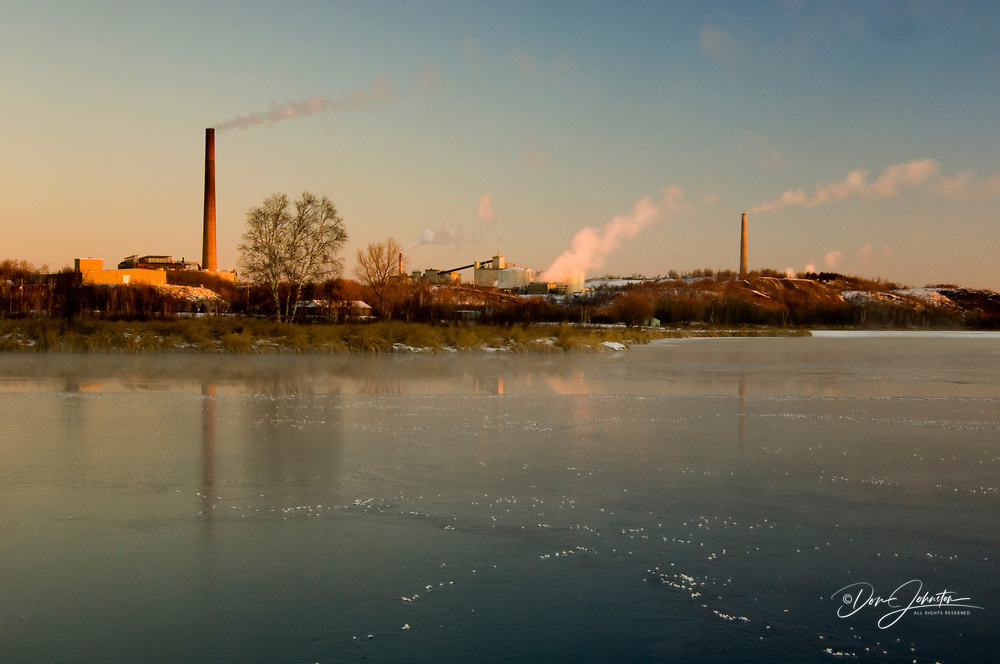 INCO/CVRD Superstack and smelter reflected in fresh ice on Kelly Lake at dawn, Sudbury, Ontario, Canada