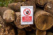 Do not climb on timber stacks sign on pile of logs, Sutton, Suffolk, England, UK
