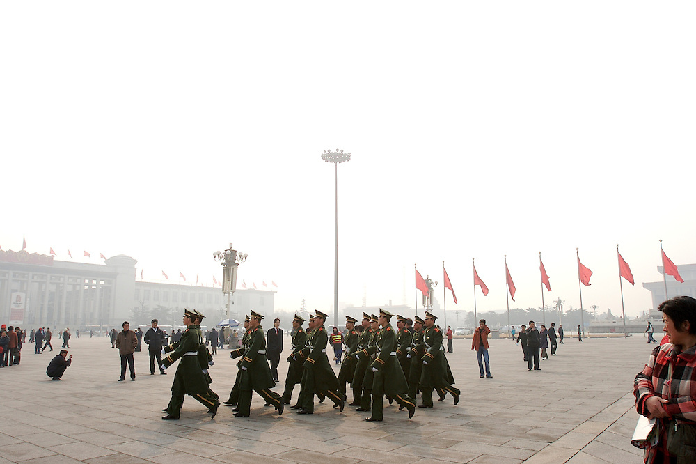One group of soldiers exit Tiananmen Square while another enters from a different side during guard rotation in Beijing, China.