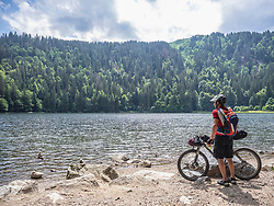 Mountain biker resting at lake Feldsee near Mt Feldberg, Baden-Wuerttemberg, Germany