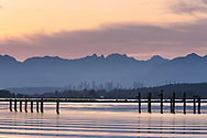 Waves roll across the Nicomekl River at sunset at Blackie Spit in Surrey, British Columbia, Canada. Burnaby's Metrotown and the North Shore (Pacific Coast Range) Mountains are in the background.