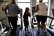 """Trainer Tiffany Gust (C) encourages Wendy Bierwirth (L) and Wendy Tonker on treadmills in the """"mountain"""" fitness class at the Biggest Loser Resort in Ivins, Utah September 6, 2010.  Guests at the resort affiliated with the popular reality television show are restricted to a daily 1,200 calorie diet and exercise 6 to 7 hours a day.  REUTERS/Rick Wilking (UNITED STATES)"""