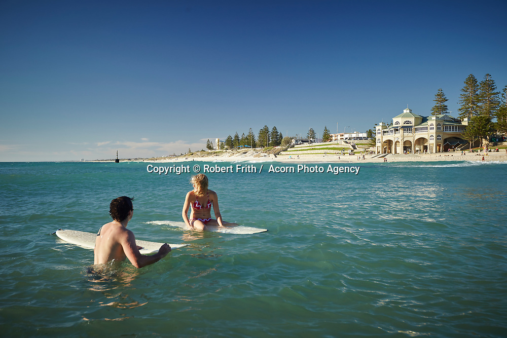 Couple on surfboards at Cottesloe Main Beach with Indiana Tearooms in the background