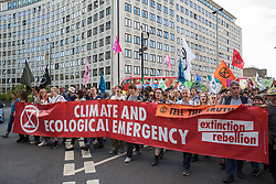 London, UK. 15 July, 2019. Climate activists from Extinction Rebellion march from the Royal Courts of Justice, where they had blocked the road for the day, to a camp site at Waterloo Millennium Green on the first day of the group's 'summer uprising', a series of events intended to apply pressure on local and central government to address the climate and biodiversity crisis.