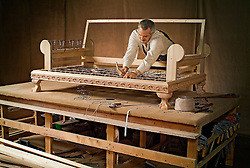 Furniture craftsman building a sofa on a work table