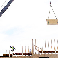 022514       Cable Hoover<br /> <br /> Construction crews guide a crane as it lowers a load of lumber onto the top upper levels of the new Best Western Hotel near downtown Gallup Tuesday.