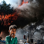 MORIA, GREECE - SEPTEMBER 10: An Afghan asylum seeking boy waits for his father to retrieve random tarps from spared tents while making their way to safety as fires, which started Wednesday morning, continue to rage into Thursday morning inside of Moria camp on September 10, 2020 in Moria. According to UNHCR, current numbers say the asylum-seekers displaced from the encampment are around 12,000. (Photo by Byron Smith/Getty Images)