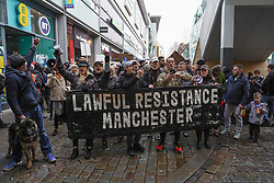 © Licensed to London News Pictures. 12/12/2020 Manchester, UK. Protesters hold placards and shout slogans during an anti-lockdown as they march through the streets of Manchester. Hundreds  of protesters gathered at Piccadilly Circus to protest against Covid-19 restrictions. Photo credit: Ioannis Alexopoulos/LNP