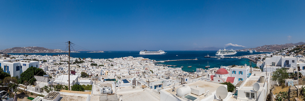 Panoramic view of Mykonos town with white houses and sailing cruise ships in blue sea on sunny day in Greece