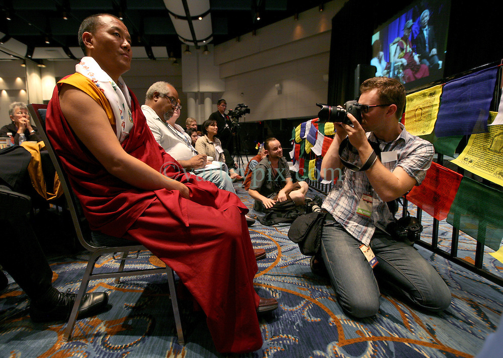 17 May 2013. New Orleans, Louisiana,  USA..Photographer Pawel Wyszomirski photographs a Buddhist Monk as His Holiness the 14th Dalai Lama in speaks at the 'Resiliance - Strength through Compassion and Connection' conference. .Photo; Charlie Varley.