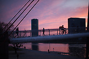 "Germany banned gatherings of more than 2 people called ""social distancing"" because of the coronavirus. People crossing a bridge above river Main in Frankfurt which is very empty on a - normally very busy - Thursday evening."