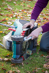 Using a brush to clean dirt and grass off mower blades before winter