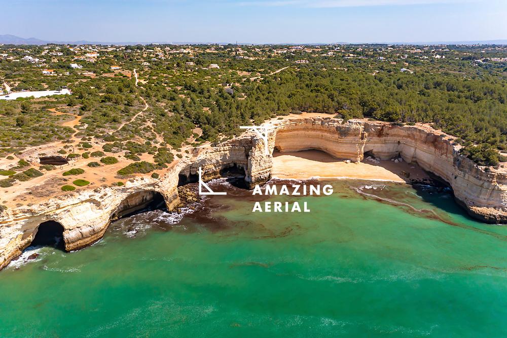 Aerial view of Praia da Corredoura beach along the cliffs and caves on the coast of Lagoa, Algarve, Portugal.