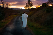 Priest wearing a white habbit walking and mediating along a small country road at dusk in Lagrasse, France. The Abbey of St. Mary of Lagrasse is a Romanesque abbey in Lagrasse, southern France. The priests, live in common under the Rule of St. Augustine, and dedicate their lives to the liturgy, which they celebrate in the pre-Vatican II form, and to evangelization. Common life, contemplative life, and apostolic life form the three facets of their charism.