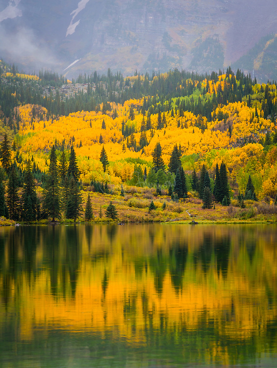 """The Maroon Bells are two peaks in the Elk Mountains, Maroon Peak and North Maroon Peak, separated by about a third of a mile. The mountains are about 12 miles southwest of Aspen. Both peaks are fourteeners. Maroon Peak, at 14,156 feet, is the 27th highest peak in Colorado; North Maroon Peak, at 14,014 feet, is the 50th highest. The view of the Maroon Bells to the southwest from the Maroon Creek valley is one of the most famous scenes in Colorado, and is reputed to be the """"most-photographed spot in Colorado"""" and one of Colorado's premier scenic overlooks. The peaks are located in the Maroon Bells-Snowmass Wilderness of White River National Forest.<br /> <br /> A US Forest Service sign on the access trail refers to these mountains as """"The Deadly Bells"""" and warns would-be climbers of """"downsloping, loose, rotten and unstable"""" rock that """"kills without warning"""". Unlike other mountains in the Rockies that are composed of granite and limestone, the Bells are composed of metamorphic sedimentary mudstone that has hardened into rock over millions of years. Mudstone is weak and fractures readily, giving rise to dangerously loose rock along almost any route. The mudstone is responsible for the Bells' distinctive maroon color. The Bells got their """"deadly"""" name in 1965 when eight people died in five separate accidents.<br /> <br /> Maroon Lake (9,580') occupies a basin that was sculpted by Ice-Age glaciers and later dammed by landslide and rockfall debris from the steep slopes above the valley floor."""