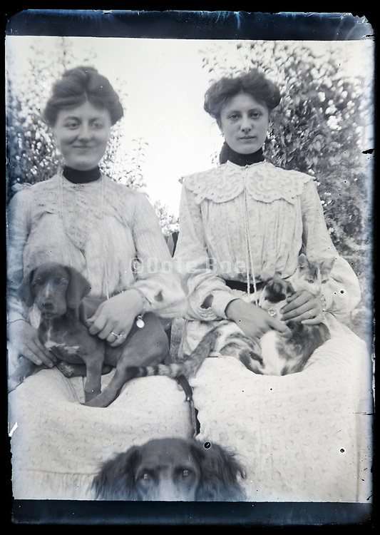 two elegant dressed ladies posing with pet cat and dogs France circa 1920s