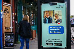 "© Licensed to London News Pictures. 26/09/2020. London, UK. A woman walks past 'Protect your loved ones. Get the App' digital advert in north London, which is a part of the government's new public information campaign on NHS COVID-19 Track And Trace App. The app was launched early this week after months of delay and questions about its effectiveness. Health Secretary MATT HANCOCK said that, ""Every single person who downloads the app is helping to improve how it can keep us safe. It helps you to keep yourself and your loved ones safe."" Users who have tested negative for COVID-19 are unable to input and share the results on the NHS app, if they did not book the test via the app in the first place. Photo credit: Dinendra Haria/LNP"