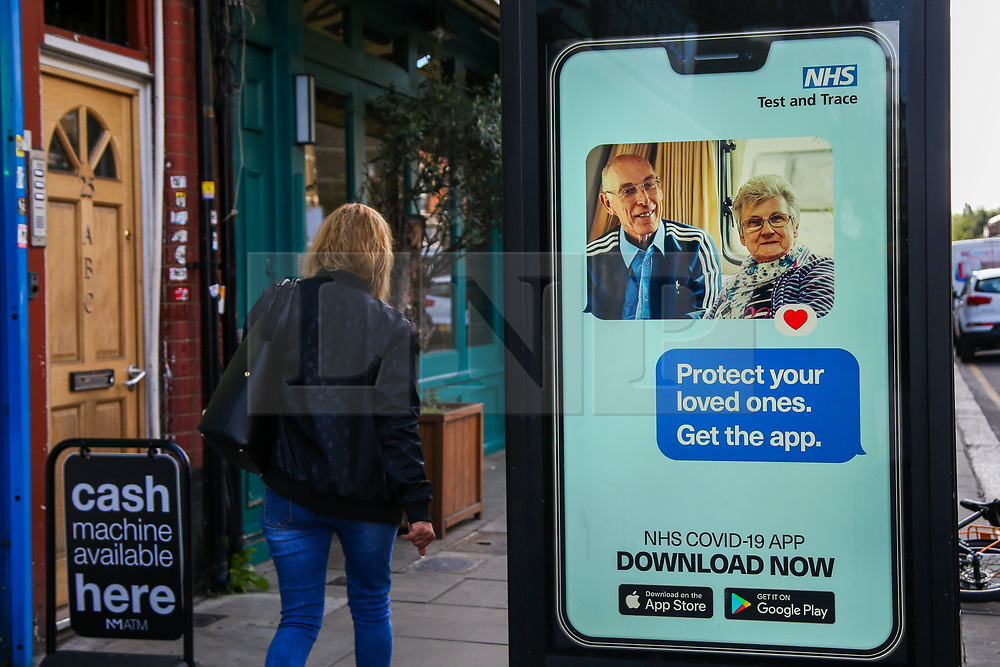 """© Licensed to London News Pictures. 26/09/2020. London, UK. A woman walks past 'Protect your loved ones. Get the App' digital advert in north London, which is a part of the government's new public information campaign on NHS COVID-19 Track And Trace App. The app was launched early this week after months of delay and questions about its effectiveness. Health Secretary MATT HANCOCK said that, """"Every single person who downloads the app is helping to improve how it can keep us safe. It helps you to keep yourself and your loved ones safe."""" Users who have tested negative for COVID-19 are unable to input and share the results on the NHS app, if they did not book the test via the app in the first place. Photo credit: Dinendra Haria/LNP"""