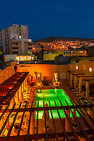 Looking over the pool of the Movenpick Resort Petra at twilight with the city behind, Petra (Wadi Musa), Jordan.