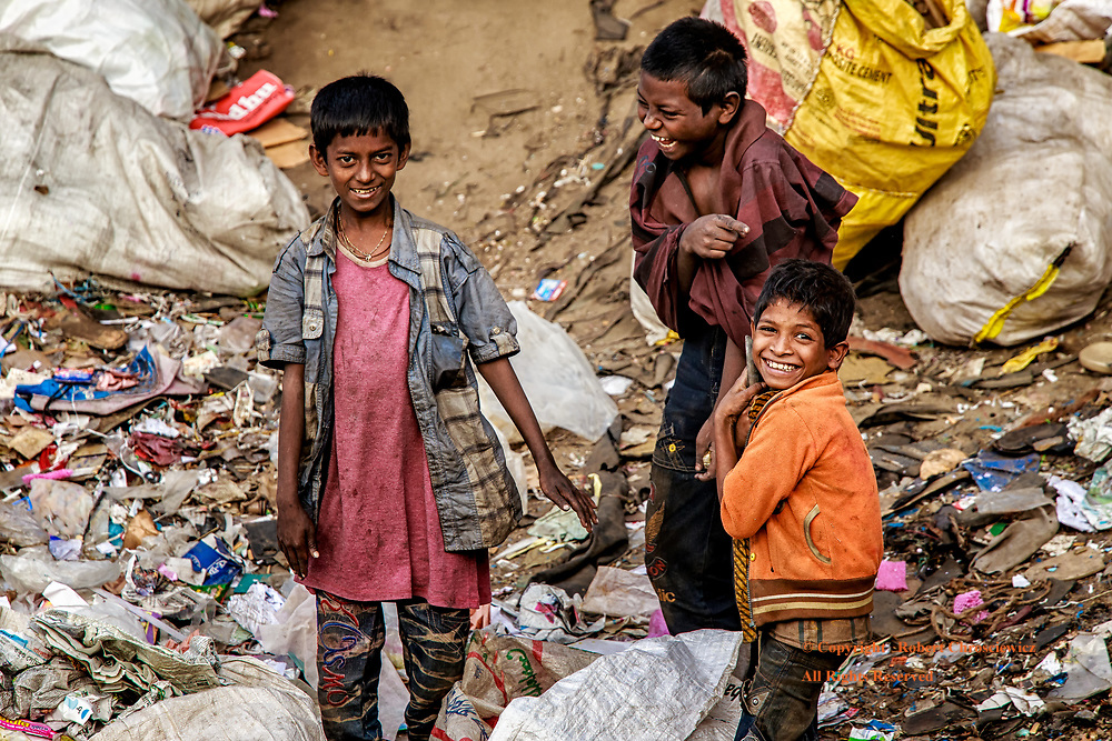 Friends Through the Worst of Times: Three young friends share a moment of glee in amongst the garbage on the riverside loading dock shores, Dhaka Bangladesh.