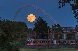 © Licensed to London News Pictures. 05/06/2020. LONDON, UK. A train passes by as June's full moon, known as a Strawberry Moon, rises behind Wembley Stadium's arch in north west London.  June's full moon, according to The Old Farmer's Almanac, was the signal for Native American Algonquin tribes to harvest wild strawberries.  This month's full moon also coincides with a subtle penumbral eclipse, which occurs when the Earth casts a slight shadow over the Moon.  Photo credit: Stephen Chung/LNP
