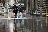A man is seen braving the rain to exercise in the CBD during COVID-19 in Melbourne, Australia. Victoria has recorded 14 COVID related deaths including a 20 year old, marking the youngest to die from Coronavirus in Australia, and an additional 372 new cases overnight. (Photo by Dave Hewison/Speed Media)