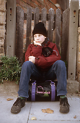 Young boy sitting on kit bag in front of wooden gate after running away from home,