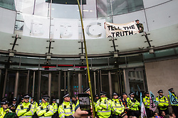 London, UK. 11 October, 2019. Climate activists from Extinction Rebellion hold a banner reading 'Tell the Truth' on the glass parapet above the main entrance to the BBC's New Broadcasting House on the fifth day of International Rebellion protests. They were demanding that the broadcaster 'tell the truth' regarding the climate emergency.