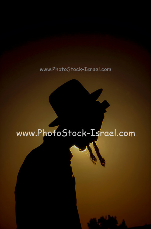 silhouette of a Jewish ultra religious man in traditional dress with hat and sidecurls, the light source is behind the man