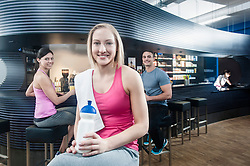 Smiling young woman at the bar of a gym