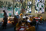 Inside a classroom at South Farnborough Infant School, Hampshire, UK.  The female teacher is arranging a new classroom display while the young children sit and work at their tables.