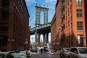 The Empire State Building framed by Manhattan Bridge which is framed by the red brick buildings of Washington Street, Dumbo, Brooklyn, New York City, United States of America.  People walk across the street, which still has cars surrounded in snow.