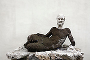 ancient sculpture of which body covered in moss Rome Italy