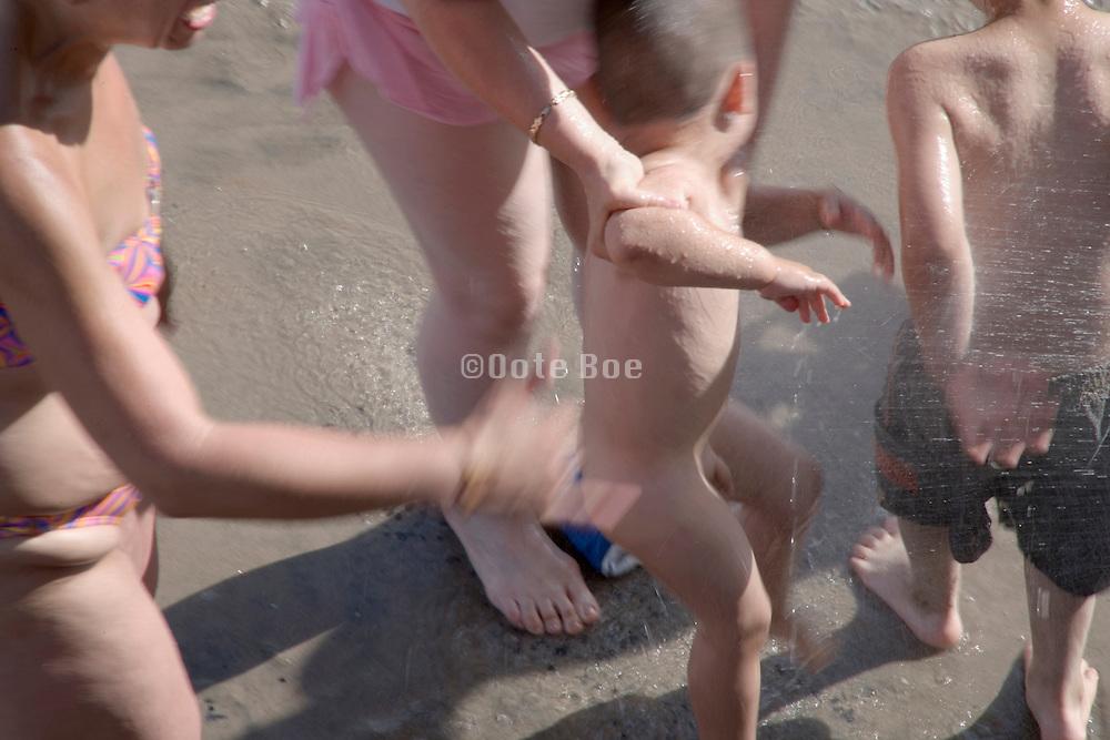a little child being showered on a sandy beach