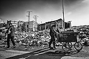 A street vendor passes by the trash mountain. There are tons of trash and garbage dumped on the streets due to the lack of public services, which causes deterioration in public health.