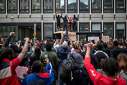 """© Licensed to London News Pictures. 03/06/2020. London, UK. Protesters hold up their fists on top of a bus stop in central London during a """"Justice for Black Lives"""" demonstration. Protests have taken place across the United States and in cities around the world in response to the killing of George Floyd by police officers in Minneapolis on 25 May. Photo credit: Rob Pinney/LNP"""