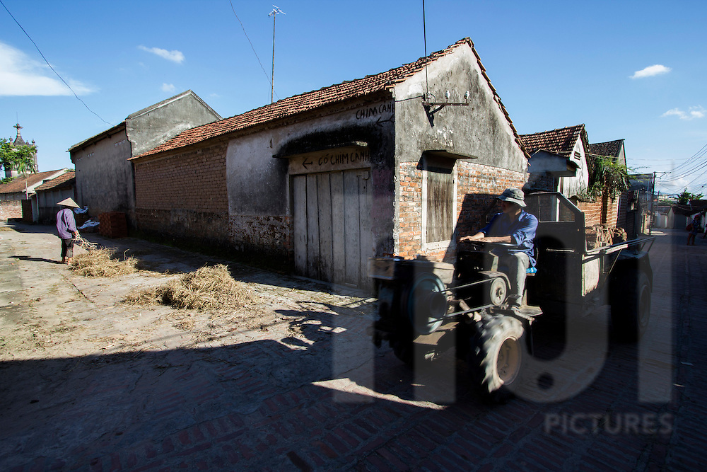 Local man drives a tractor through the ancient village of Duong Lam, Son Tay Town, Hanoi outskirts, Vietnam, Southeast Asia