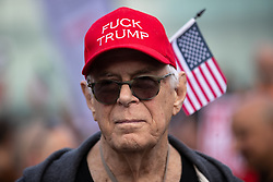 © Licensed to London News Pictures . 03/06/2019. Manchester, UK. An American man wearing a FUCK TRUMP red baseball cap and American flag in the crowd . A Manchester Together Against Trump demonstration in Cathedral Gardens , central Manchester , during the first day of US President Donald Trump's visit to the UK . Photo credit: Joel Goodman/LNP