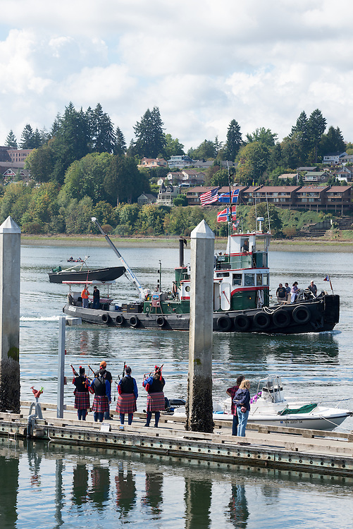Bagpipers playing for people on tugboats during the annual Olympia Harbor Days festival in Olympia, Washington.