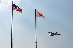 """A U.S. Air Force C-130J Super Hercules assigned to the 36th Airlift Squadron flies over Yokota Air Base, Japan, July 18, 2018, during a """"fini-flight"""" for Col. Kenneth Moss, 374th Airlift Wing commander. The """"fini-flight"""" marked Moss's final flight as a commander of the 374th AW. (U.S. Air Force photo by Yasuo Osakabe)"""