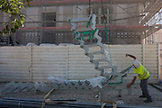 A construction worker signals to a crane operator to hoist some metal stairs into a restored building in Bairro Alto, Lisbon, Portugal.