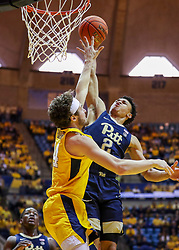 Dec 8, 2018; Morgantown, WV, USA; Pittsburgh Panthers guard Trey McGowens (2) attempts to dunk over West Virginia Mountaineers guard Chase Harler (14) during the first half at WVU Coliseum. Mandatory Credit: Ben Queen-USA TODAY Sports
