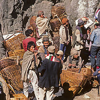 Hindu men from Nepal's lower hills rest after selling basketfuls of goods they have carried up to the weekly Saturday market in Namche Bazaar, the Himalaya's leading Sherpa town.