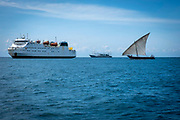 A small sail fishing boat on the sea between the Mapinduzi II passenger and cargo ship and the Bo Yuan, an industrial Chinese fishing boat outside the port of Stone Town and Zanzibar, Tanzania.